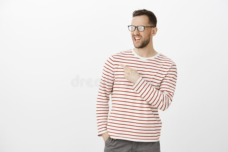 That guy is strange. Disgusted displeased adult man in glasses, spreading rumor or discussing person who stands back stock photo