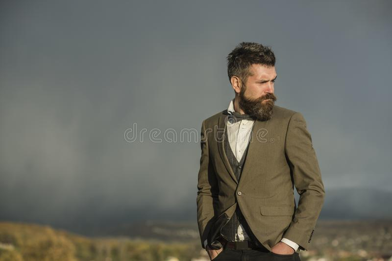 Guy with strict face enjoys scenery and view. Hipster with stylish appearance in front of dramatic sky, skyline. Man with beard and mustache on top of mountain stock photo