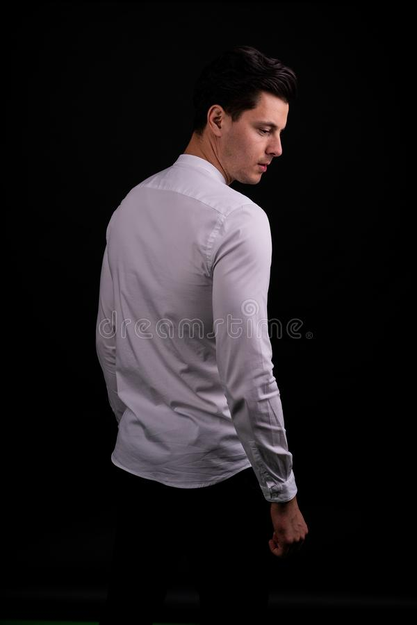 The guy is struggling with problems from the past. Man on black background in Studio. serious royalty free stock image