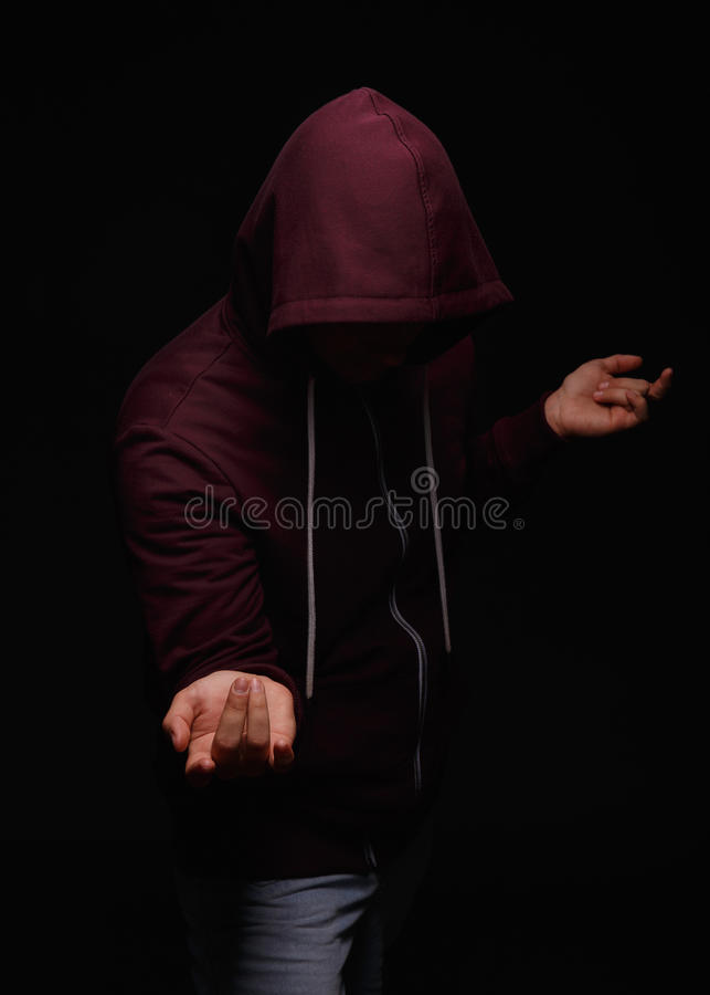 The guy suffering from alcoholism in a hood on a black background. Bad, alcohol, unhealthy, risk concept. royalty free stock photography