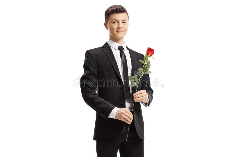 Guy in a suit holding a red rose and smiling at the camera royalty free stock photo