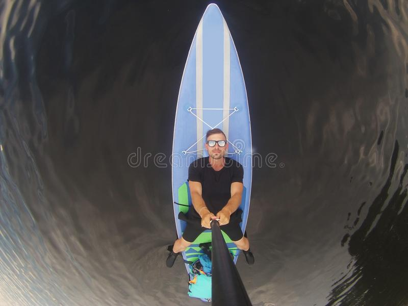 Guy in sunglasses lying on puddle boarding top view, SUP serf, stock photography
