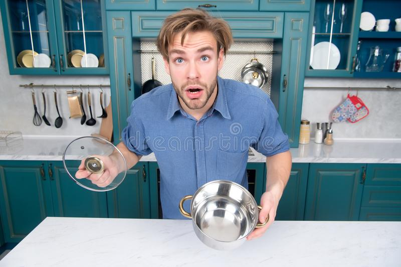 Guy with surprised face hold open saucepan, lid in kitchen. Man with cooking pot for stew, soup dishes. Cuisine cooking, food preparation. Cookware, tool royalty free stock image