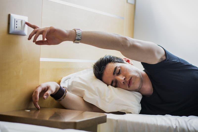 Guy Switching cansado de la luz mientras que miente en cama imagen de archivo libre de regalías