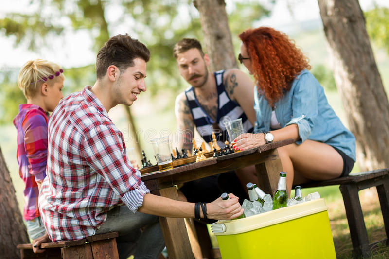 Guy takes out cold beer from handheld refrigerator. Guy on picnic in forest takes out cold beer from handheld refrigerator royalty free stock photography