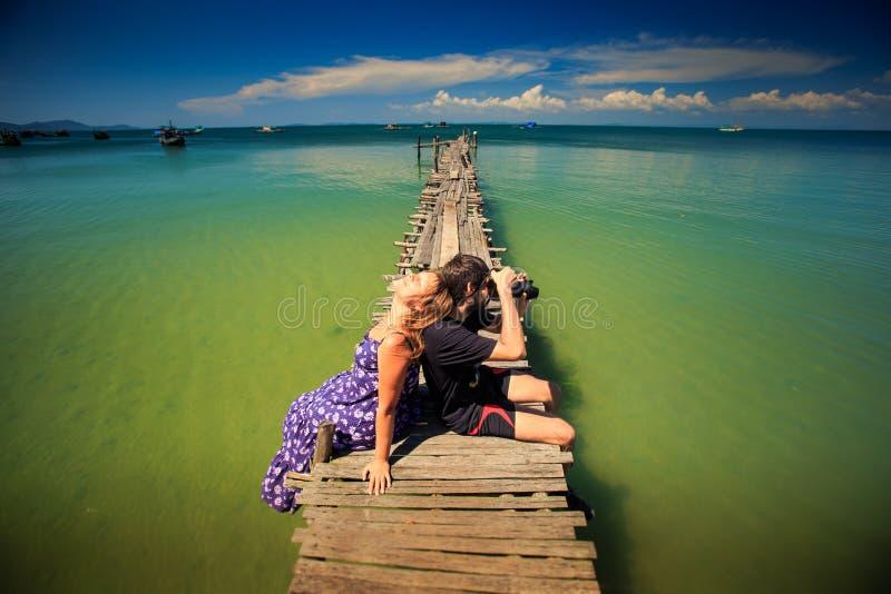 Guy Takes Photo Girl Sits op Pijler tegen Oceaan royalty-vrije stock foto's