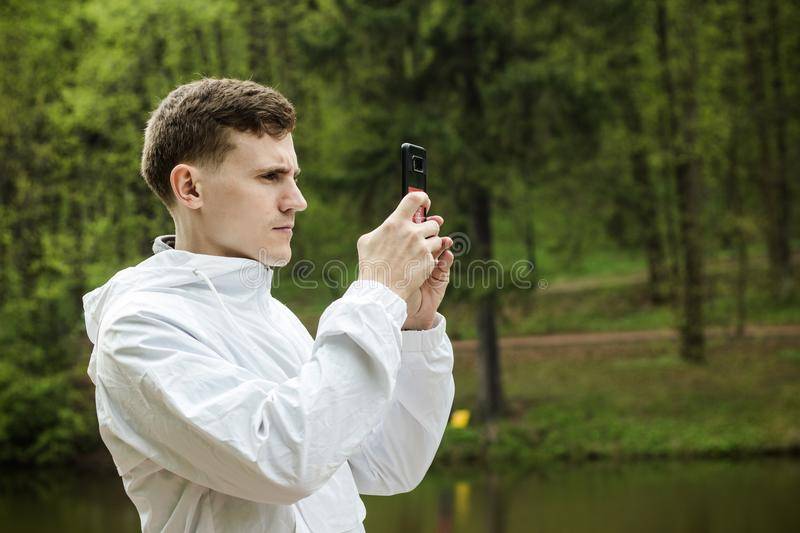 Guy takes pictures of nature on the phone, walk royalty free stock photo