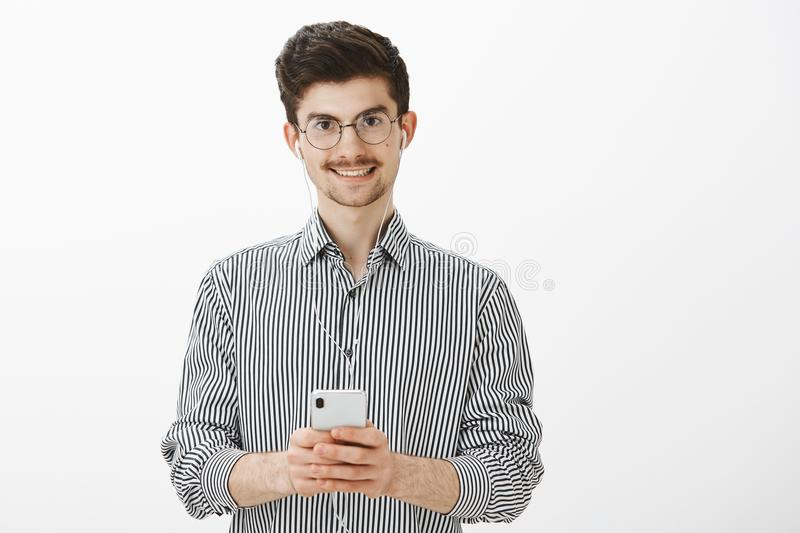 Guy taking notes while listening audiobook. Portrait of friendly attractive caucasian man with moustache and beard stock photography