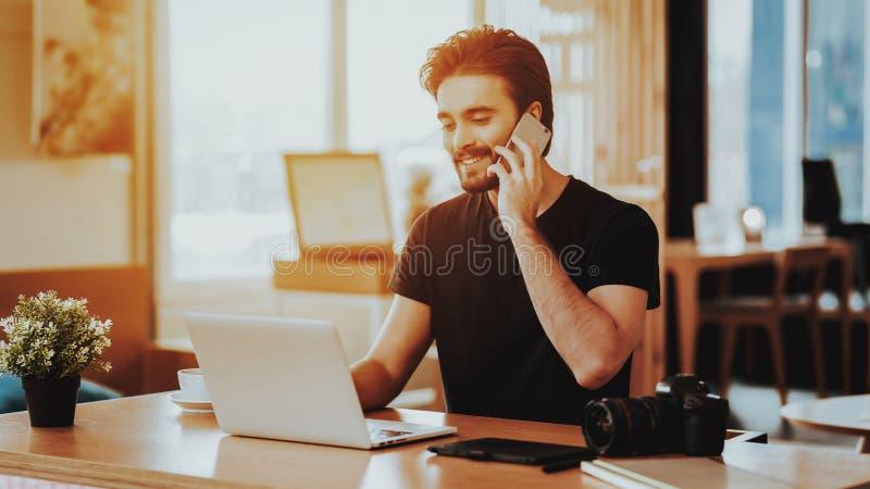 Guy Talks Phone heureux et travailler sur l'ordinateur portable à distance photographie stock libre de droits