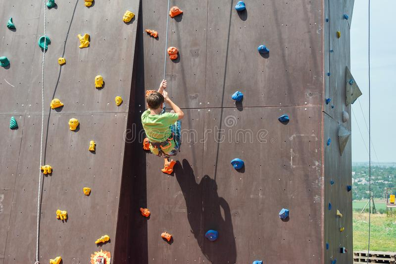 The guy the teenager slazits from an artificial rock with the help of a safety rope, is engaged in rock-climbing. stock photos