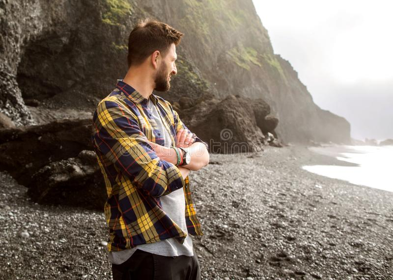 Guy tourist standing on the beach at sunset in Iceland in checkered shirt.  stock photos