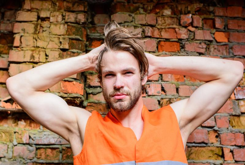 Guy tousled hair stand in front of wall made out of red bricks. Builder orange vest work construction site. macho stock photos