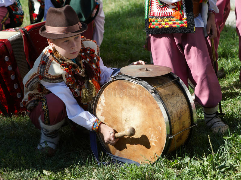 guy in a traditional comedy of Ukrainian highlanders Hutsuls plays a drum during the Brynza Festival (Hutsul Sheep Cheese) in stock photos