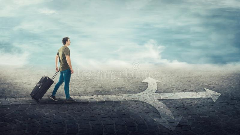 Guy traveler carrying his rolling suitcase, walking on a crossroad line split in three different ways as road arrows royalty free stock photography