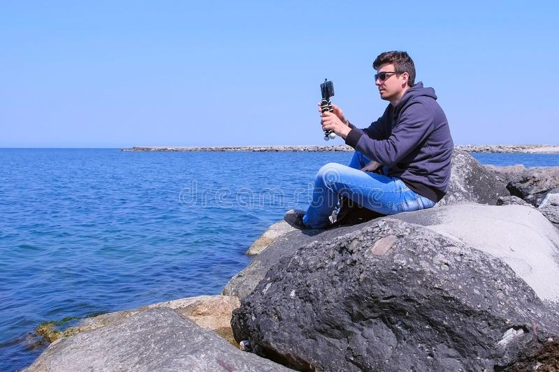 Man starts to record video on smartphone with tripod sits on huge stone at sea. stock images