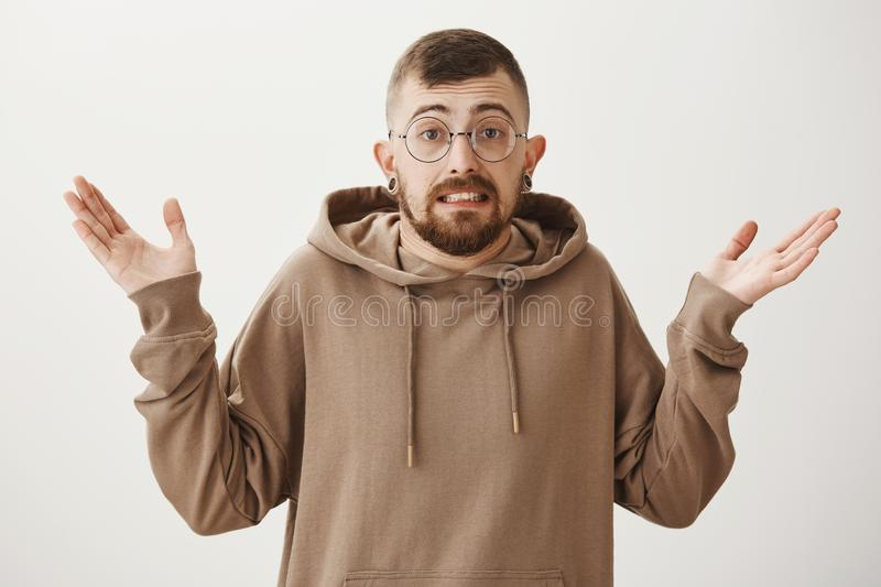 Guy tries to pretend innocent and clueless. Portrait of guilty lying handsome guy in transparent glasses shrugging with. Spread hands, showing teeth, being royalty free stock image