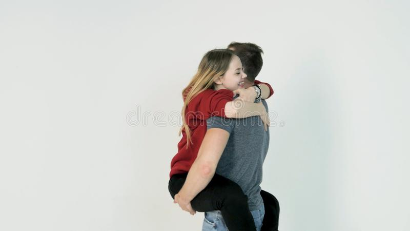 Guy turns the girl on hands. Young man turns the girl on hands on white background royalty free stock photo