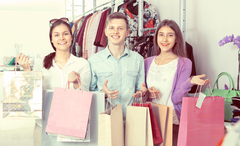 Guy and two girls holding bags. Russian guy and two girls holding bags with clothes in apparel store royalty free stock photo
