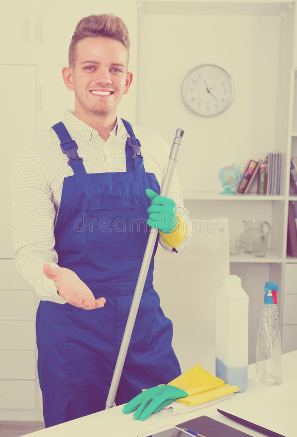 Guy in uniform cleaning in office stock images