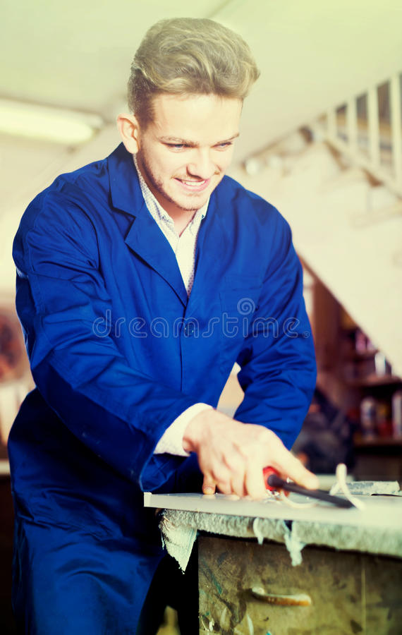 Guy using chisel to process plank at workshop. Young american guy using chisel to process plank at workshop stock photo