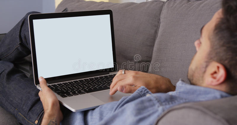 Guy using laptop on couch. Mexican guy using laptop on couch royalty free stock photography