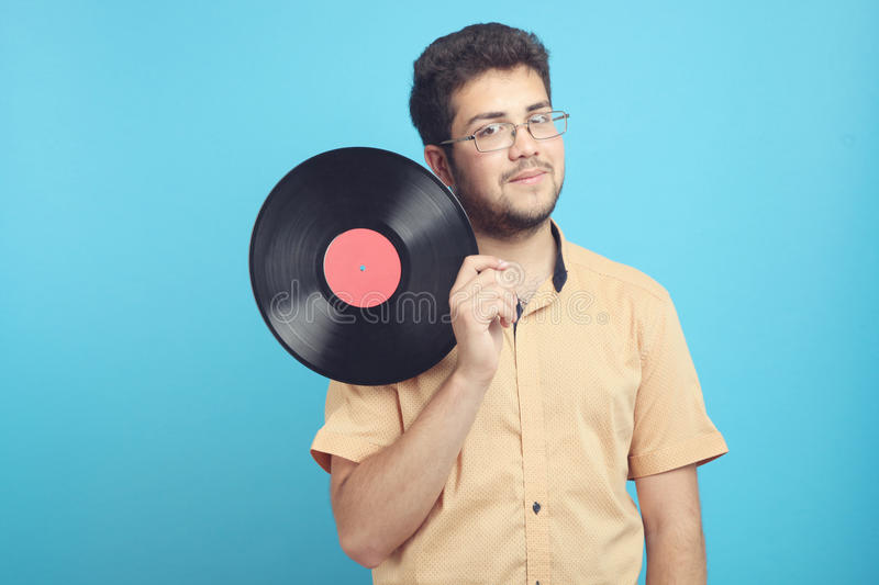 Guy with a vinyl record. A guy with a vinyl record on a blue background stock images