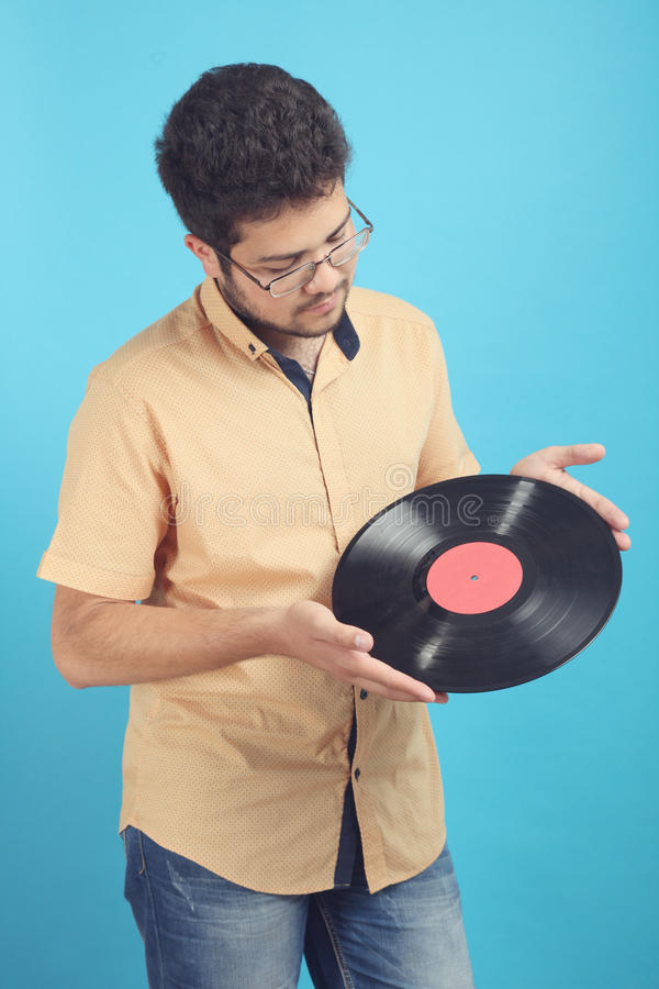 Guy with a vinyl record. A guy with a vinyl record on a blue background stock photos