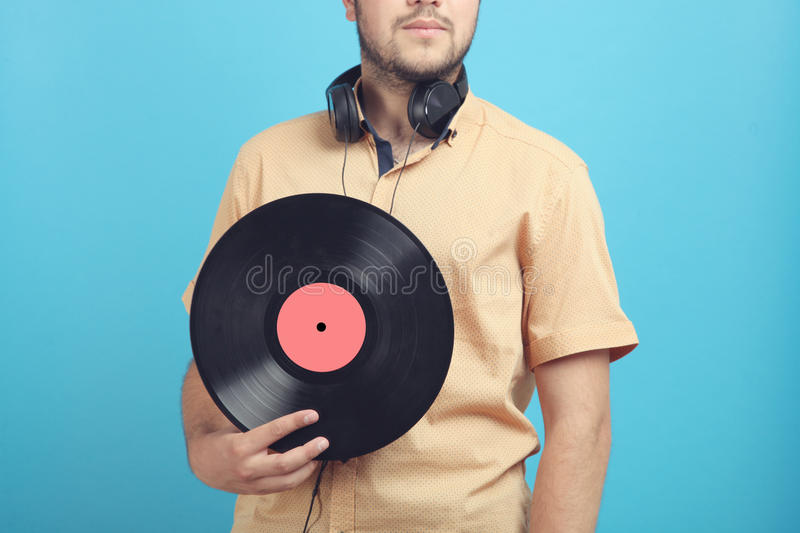 Guy with a vinyl record. And in headphones on a blue background royalty free stock image