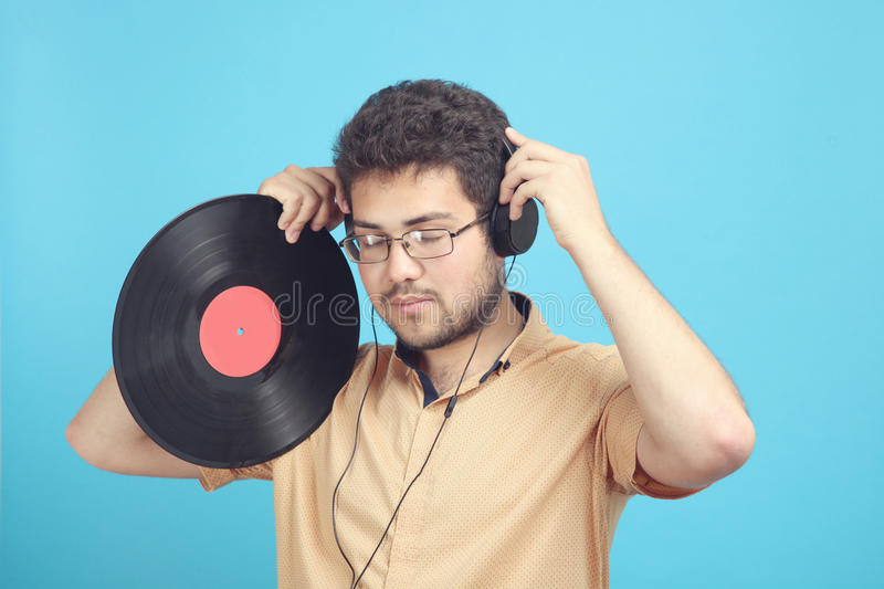Guy with a vinyl record. And in headphones on a blue background royalty free stock photos