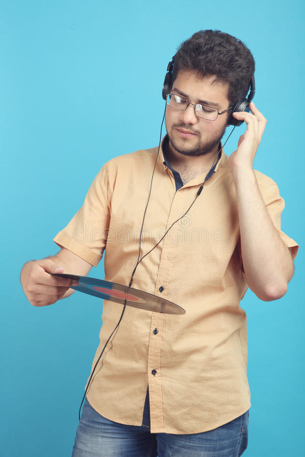 Guy with a vinyl record. And in headphones on a blue background stock photography