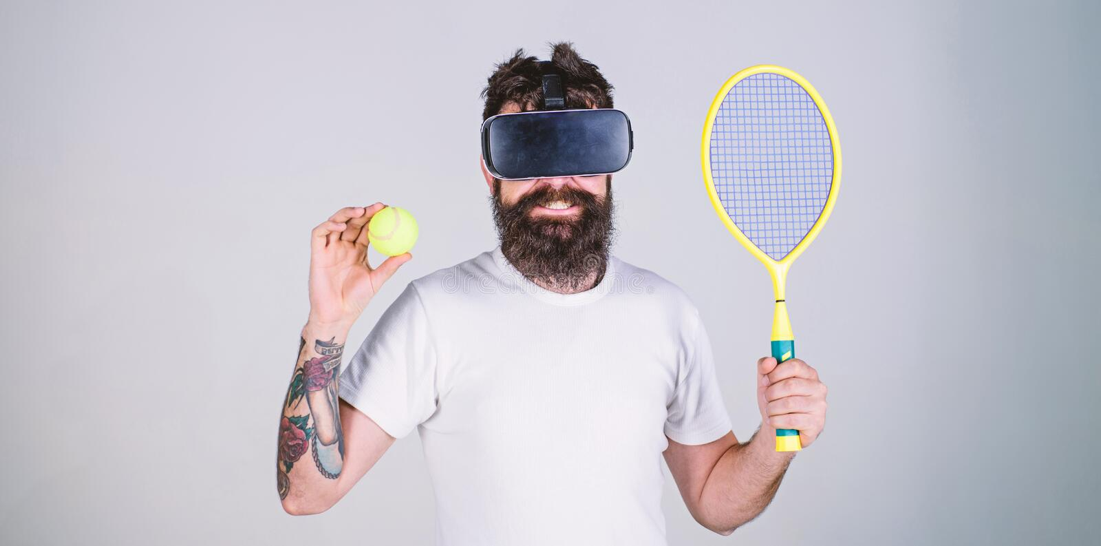 Guy with VR glasses play tennis with racket and ball. Man with beard in VR glasses play tennis, grey background. Hipster. On smiling face use modern technology royalty free stock photos