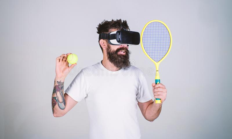 Guy with VR glasses play tennis with racket and ball. Man with beard in VR glasses play tennis, grey background. Virtual. Sport concept. Hipster on smiling face stock photography