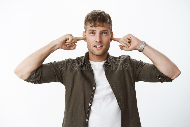 Guy waiting for big blow closing ears with index fingers not hear loud sound looking with anticipation up open mouth in stock images