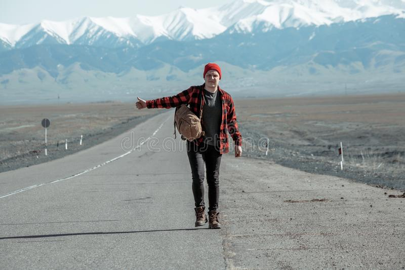 Guy walking on long old mountain road. Guy dressed in red shirt and black jeans walking down on long old mountain road stock photo