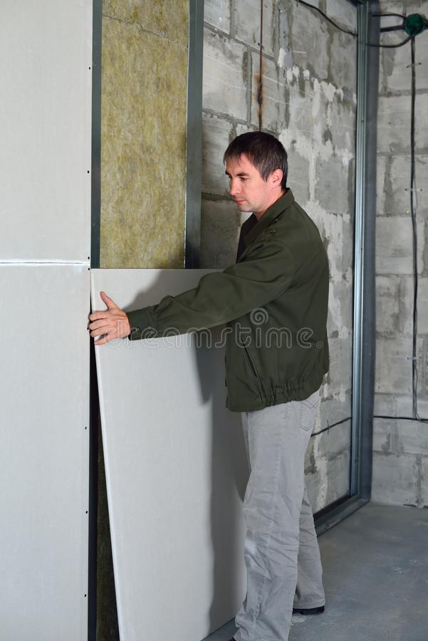 The guy warms the wall. Man performs works on warming the room stock images