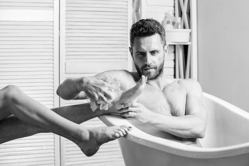 Guy wash female legs with foam sponge. macho enjoying bath. Sexy man in bathroom. Sex and relaxation concept. Macho. Naked in bathtub. Wash off foam with water royalty free stock photos