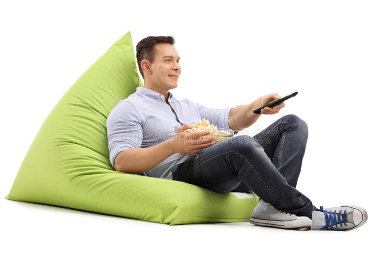 Guy watching TV seated on a beanbag stock photos