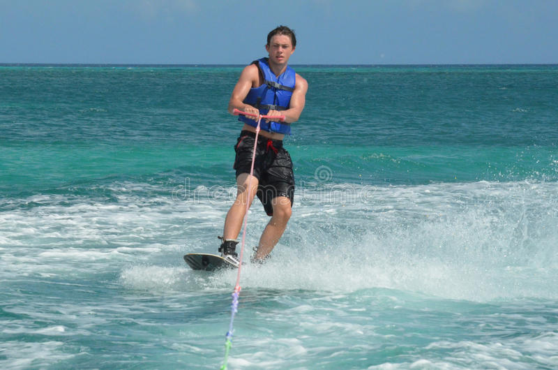 Guy Wearing a Blue Life Vest Wakeboarding in Aruba. Young guy in a blue life vest wakeboarding stock photo