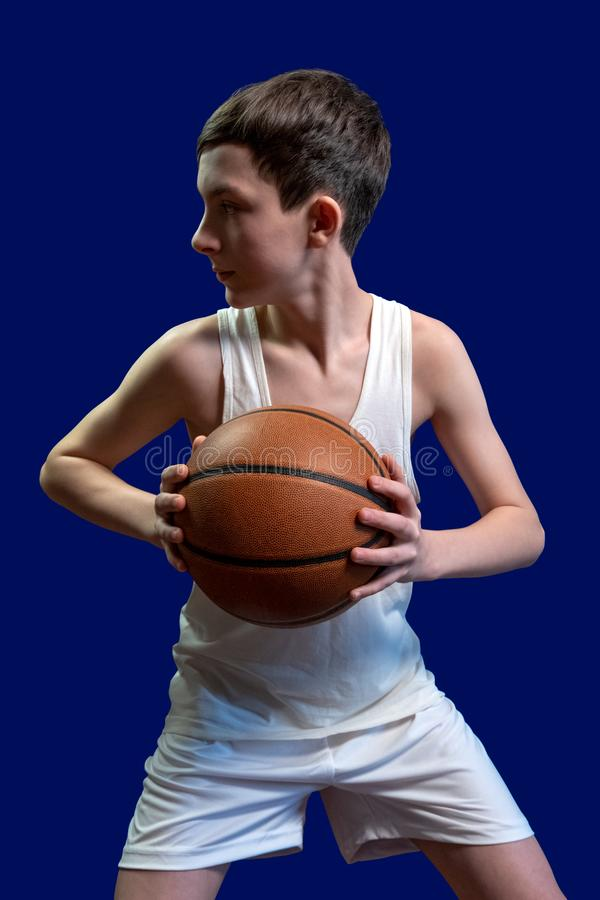 The guy in the white T-shirt with a basketball ball on a blue background. Sports teenager. Sport, game, health, lifestyle royalty free stock photos