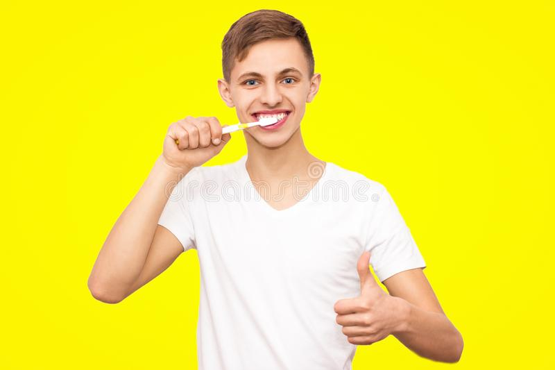 A guy in a white T-shirt brushing his teeth, isolated on a yellow background royalty free stock photo
