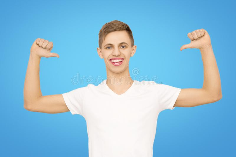 A guy in a white T-shirt with his hands up in the studio on a blue background, isolate stock image