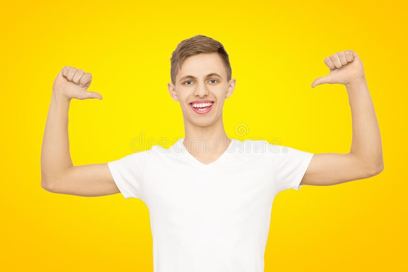 A guy in a white T-shirt with his hands up in the studio on a yellow background, isolate stock image