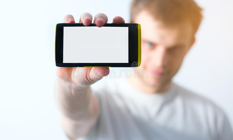 Guy in white t-shirt holding a smart phone in his hand on a whit stock photos