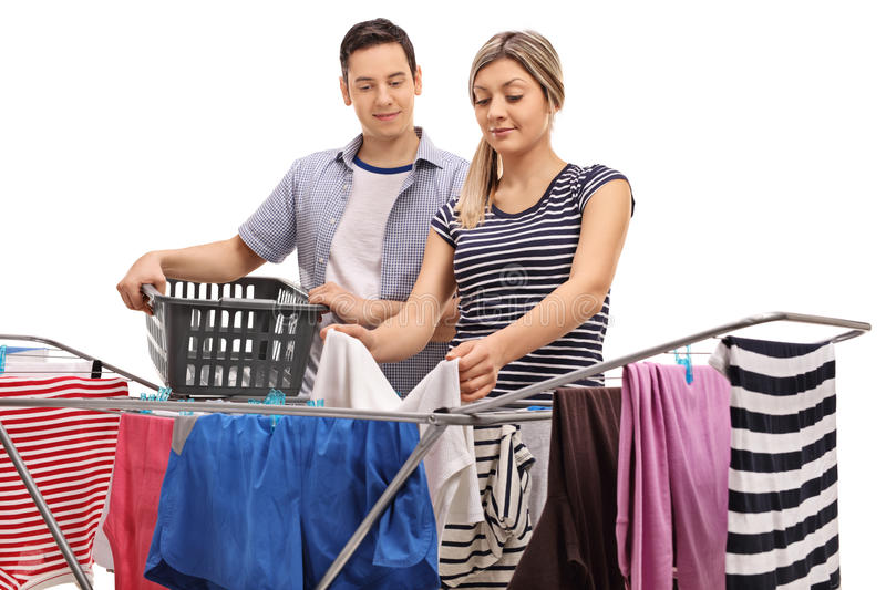 Guy with a woman picking up clothes from rack dryer stock image