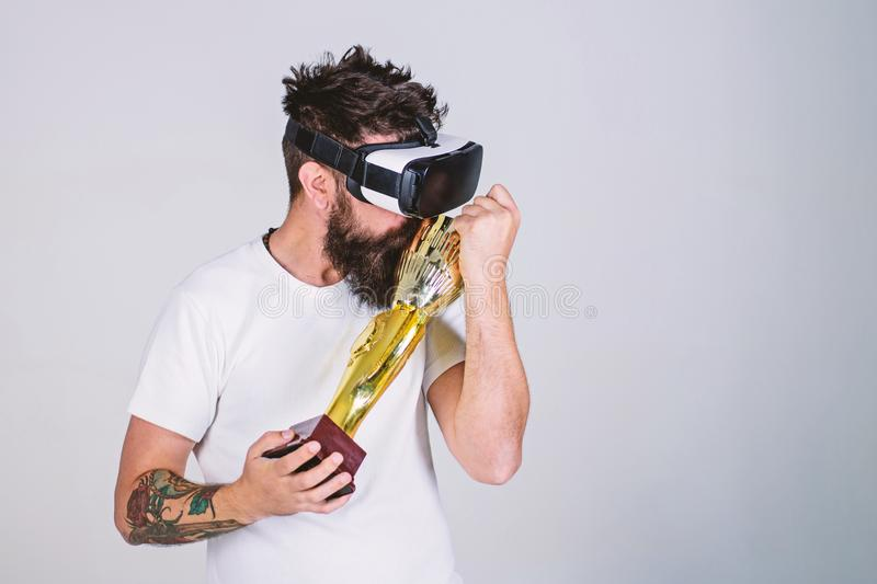 Guy won virtual competition and carries on shoulder goblet. Hipster on grateful face kisses goblet. Champion concept. Man with beard in virtual reality glasses royalty free stock images