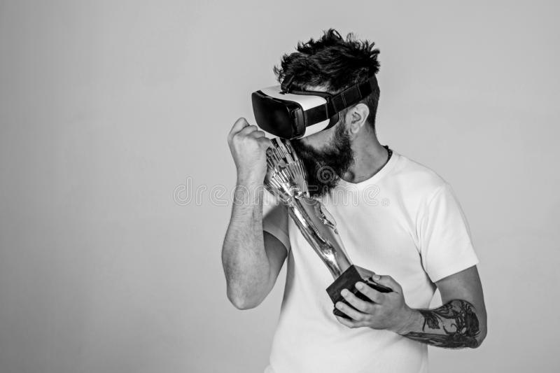 Guy won virtual competition and carries on shoulder goblet. Hipster on grateful face kisses goblet. Champion concept. Man with beard in virtual reality glasses royalty free stock photos