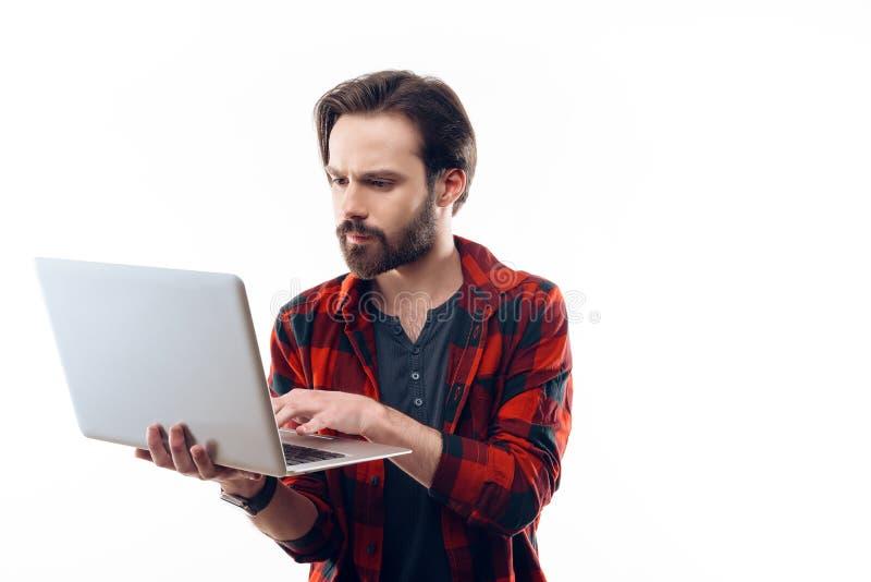 Guy Working barbudo joven serio en el ordenador portátil fotografía de archivo