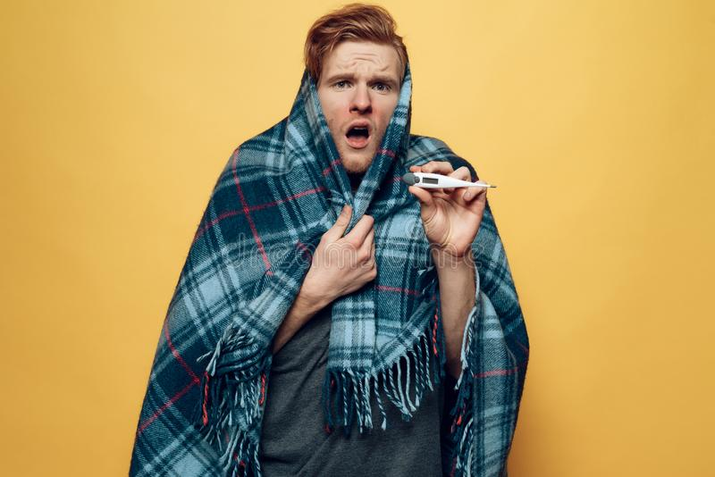 Guy Wrapped die in Plaid op Thermometer richten stock foto