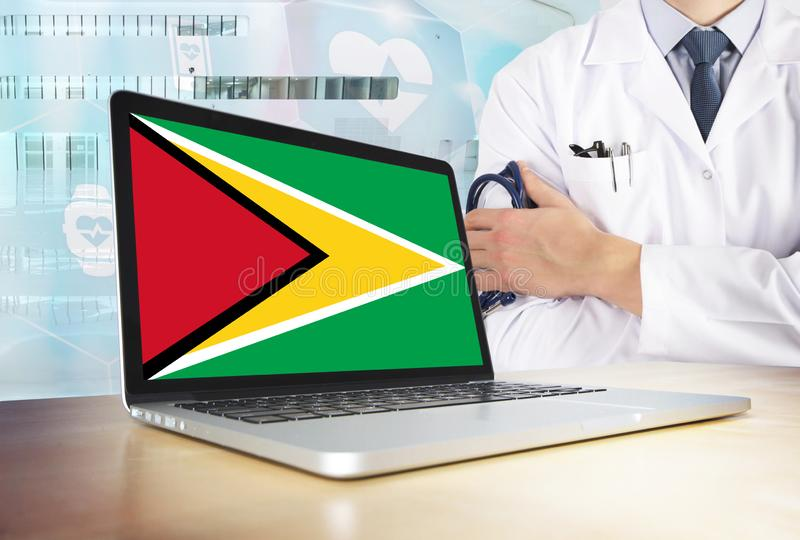 Guyana healthcare system in tech theme. Guyanese flag on computer screen. Doctor standing with stethoscope in hospital. Cryptocurrency and Blockchain concept royalty free stock image