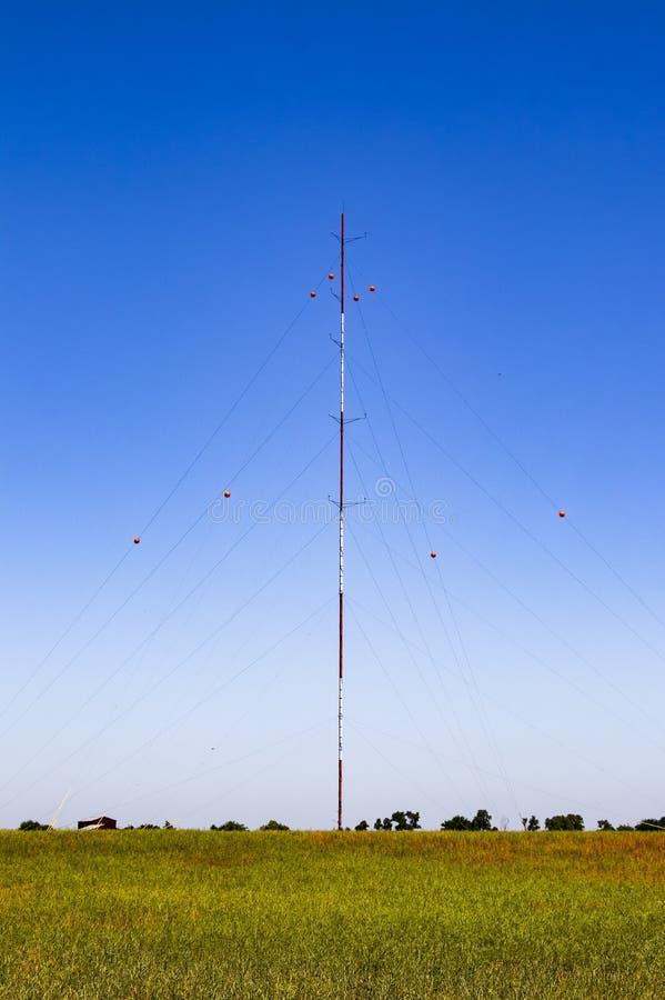 Guyed radia el radiador del palo para las telecomunicaciones y la difusión con los aisladores rojos de la porcelana en los alambr foto de archivo libre de regalías